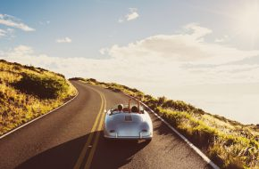 Happy Couple Driving on Country Road in Classic Vintage Sports Car